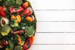 Τα περισσότερα χρήσιμα λαχανικά είναι μπρόκολο, κρεμμύδια, σκόρδο, ντομάτες, καρότα που τεμαχίζονται με τα πράσινα σε ένα μαύρο π Στοκ Εικόνα