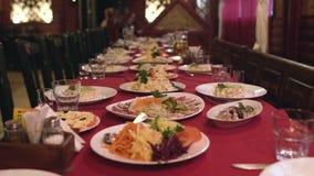 Τα πιάτα των τροφίμων και οι σαλάτες είναι στον πίνακα στο εστιατόριο ή τον καφέ, πίνακας συμποσίου για το εταιρικό γεύμα φιλμ μικρού μήκους