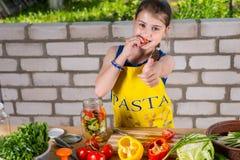 Τα πιπέρια δειγματοληψίας κοριτσιών και το δόσιμο φυλλομετρούν επάνω Στοκ φωτογραφίες με δικαίωμα ελεύθερης χρήσης