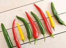 Τα πιπέρια τσίλι είναι σε μια σειρά - κίτρινο, πράσινο και κόκκινο πιπέρι τσίλι Στοκ Εικόνες