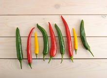 Τα πιπέρια τσίλι είναι σε μια σειρά - κίτρινο, πράσινο και κόκκινο πιπέρι τσίλι Στοκ Φωτογραφία