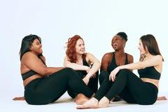 Τα πολυφυλετικά θηλυκά με το διαφορετικά μέγεθος και το έθνος στέκονται μαζί και χαμογελούν στοκ εικόνα