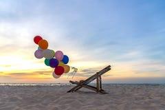 Τα πολύχρωμα μπαλόνια με το κρεβάτι καμβά για χαλαρώνουν ηλιόλουστη ημέρα παραλιών ηλιοβασιλέματος την τροπική Στοκ Εικόνες