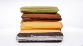 Τα πολύχρωμα μπισκότα σάντουιτς πλάγιας όψης περιστρέφονται και σταματούν στο λευκό φιλμ μικρού μήκους