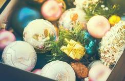 Τα πολύχρωμα παιχνίδια Χριστουγέννων, κατασκευασμένες σφαίρες βρίσκονται σε ένα ανοικτό κιβώτιο, επίδραση του instagram Στοκ φωτογραφία με δικαίωμα ελεύθερης χρήσης