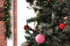 Τα πολύχρωμα παιχνίδια χριστουγεννιάτικων δέντρων κρεμούν στους κλάδους ενάντια στη διακοσμημένη πόρτα του σπιτιού Στοκ Εικόνα