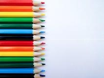 Τα πολύχρωμα φωτεινά μολύβια του ίδιου μεγέθους βρίσκονται οριζόντια στη Λευκή Βίβλο, που χωρίζεται από τα χρώματα του ουράνιου τ στοκ εικόνα