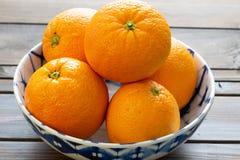 Τα πορτοκάλια επέλεξαν πρόσφατα από τα τρία έτοιμα ναφαγωθούν στον πίνακα κουζινών στοκ εικόνες
