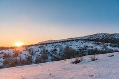 Τα πορτοκαλιά σύνολα ήλιων πέρα από το χιονισμένο βουνό Ρωσία, Stary Krym Στοκ Εικόνες