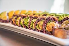 Τα πορφυρά σούσια ρυζιού κυλούν με το μάγκο και το αβοκάντο για ένα vegan γεύμα σουσιών Στοκ Φωτογραφίες