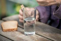Τα ποτά ηλικιωμένων γυναικών ποτίζουν και τρώνε το ψωμί σε έναν παλαιό ξύλινο πίνακα Στοκ Φωτογραφίες