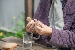 Τα ποτά ηλικιωμένων γυναικών ποτίζουν και τρώνε το ψωμί σε έναν παλαιό ξύλινο πίνακα Στοκ φωτογραφία με δικαίωμα ελεύθερης χρήσης