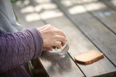 Τα ποτά ηλικιωμένων γυναικών ποτίζουν και τρώνε το ψωμί σε έναν παλαιό ξύλινο πίνακα Στοκ εικόνα με δικαίωμα ελεύθερης χρήσης