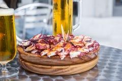 Τα ποτήρια της κρύας μπύρας και το ξύλινο πιάτο του της Γαλικίας ύφους μαγείρεψαν το χταπόδι με το ελαιόλαδο πάπρικας και gallega Στοκ Εικόνες