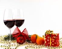 Τα ποτήρια υποβάθρου Χριστουγέννων του κρασιού στο υπόβαθρο μιας ερυθρελάτης διακλαδίζονται, κεριά και διακοσμήσεις μανταρινιών στοκ φωτογραφία με δικαίωμα ελεύθερης χρήσης