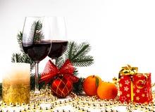 Τα ποτήρια υποβάθρου Χριστουγέννων του κρασιού στο υπόβαθρο μιας ερυθρελάτης διακλαδίζονται, κεριά και διακοσμήσεις μανταρινιών στοκ φωτογραφίες
