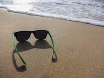 Τα πράσινα γυαλιά ηλίου τοποθετούν στην άμμο στην όμορφη παραλία και τη σκίαση του μπλε τόνου του κύματος και τον καθαρισμό της ά Στοκ Φωτογραφίες