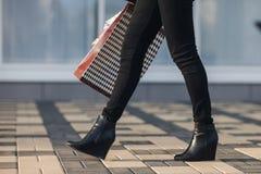 Τα προκλητικά πόδια γυναικών στα μαύρα παπούτσια πλατφορμών και τα μαύρα τζιν με τις αγορές τοποθετούν το περπάτημα στην αστική ο Στοκ φωτογραφία με δικαίωμα ελεύθερης χρήσης