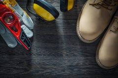 Τα προστατευτικά γάντια καλυμμάτων αυτιών στεγανοποιούν το επίπεδο ο κατασκευής μποτών Στοκ φωτογραφία με δικαίωμα ελεύθερης χρήσης