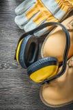 Τα προστατευτικά γάντια στεγανοποιούν τα λειτουργώντας καλύμματα αυτιών μποτών στο ξύλινο BO Στοκ Εικόνα