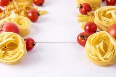 Τα προϊόντα ζυμαρικών με ντοματών το ακατέργαστο ζυμαρικών Fusili Fettuccine άσπρο υπόβαθρο τροφίμων συστατικών ιταλικό κλείνουν  Στοκ Εικόνες