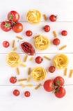 Τα προϊόντα ζυμαρικών με ντοματών το ακατέργαστο ζυμαρικών Fusili Fettuccine συστατικών ιταλικό τροφίμων άσπρο επίπεδο άποψης υπο Στοκ Εικόνες