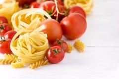 Τα προϊόντα ζυμαρικών με ντοματών τυριών το ακατέργαστο ζυμαρικών Fusili Fettuccine άσπρο υπόβαθρο τροφίμων συστατικών ιταλικό κλ Στοκ Εικόνα