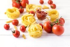 Τα προϊόντα ζυμαρικών με ντοματών τυριών το ακατέργαστο ζυμαρικών Fusili Fettuccine άσπρο υπόβαθρο τροφίμων συστατικών ιταλικό κλ Στοκ φωτογραφία με δικαίωμα ελεύθερης χρήσης