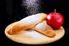 Τα πρόσφατα ψημένα γλυκά αγαθά ψεκάστηκαν με κονιοποιημένος σε ξύλινο στοκ φωτογραφία με δικαίωμα ελεύθερης χρήσης
