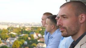 Τα πρόσωπα των επιχειρηματιών εμπιστοσύνης που εξετάζουν τη εικονική παράσταση πόλης από το μπαλκόνι και απολαμβάνουν την όμορφη  απόθεμα βίντεο