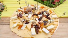 Τα πρόχειρα φαγητά από το σκληρό τυρί και οι ξηροί καρποί στο μεγάλο πιάτο κλείνουν επάνω φιλμ μικρού μήκους