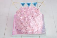 Τα πρώτα γενέθλια συνθλίβουν το κέικ Ένα ρόδινο κέικ στέκεται σε ένα άσπρο ξύλινο υπόβαθρο γενέθλια πρώτα Στοκ Εικόνες