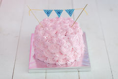 Τα πρώτα γενέθλια συνθλίβουν το κέικ Ένα ρόδινο κέικ στέκεται σε ένα άσπρο ξύλινο υπόβαθρο γενέθλια πρώτα Στοκ Φωτογραφίες