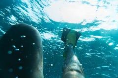 Τα πόδια ατόμων ` s είναι βατραχοπέδιλα κάτω από το νερό στοκ εικόνα