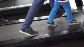 Τα πόδια γονέα που περπατούν μαζί με τα πόδια παιδιών στο τρέξιμο της συσκευής, πόδια πατέρων περπατούν κοντά στα πόδια παιδιών,  φιλμ μικρού μήκους