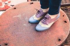 Τα πόδια γυναικών ` s στα μοντέρνα παπούτσια, ανύψωσαν το καπάκι στον κύκλο Στοκ Εικόνα