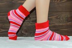 Τα πόδια γυναικών ` s στις κάλτσες στην κουβέρτα Ξύλινη ανασκόπηση Θερμές, κάλτσες stripey στοκ φωτογραφίες με δικαίωμα ελεύθερης χρήσης