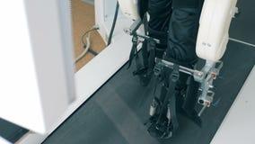 Τα πόδια ενός ανάπηρου ασθενή παίρνουν εκπαιδευμένα σε μια τρέχοντας διαδρομή προσομοίωσης απόθεμα βίντεο