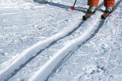 Τα πόδια ενός ατόμου που κάνει σκι στα κόκκινα εσώρουχα Χιονώδες υπόβαθρο με τα σκι και copyspace στοκ εικόνα με δικαίωμα ελεύθερης χρήσης