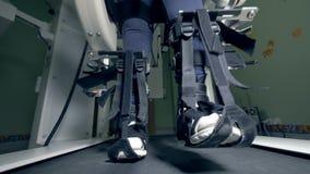 Τα πόδια ενός φυσικά προκλημένου προσώπου που δένεται με τις ζώνες κινούνται κατά μήκος της διαδρομής περπατήματος φιλμ μικρού μήκους