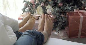 Τα πόδια ζεύγους απέναντι από το χριστουγεννιάτικο δέντρο, τον άνδρα και τη γυναίκα χαλαρώνουν τα πόδια τους κλείστε επάνω Διακοπ απόθεμα βίντεο