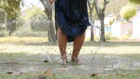 Τα πόδια κινηματογραφήσεων σε πρώτο πλάνο του κοριτσιού παιδιών πηδούν στη λακκούβα κάτω από την προβολή ύδατος στο πάρκο φιλμ μικρού μήκους