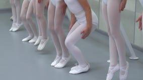 Τα πόδια κινηματογραφήσεων σε πρώτο πλάνο των μικρών ballerinas ομαδοποιούν τη στάση στη σειρά που πηδά στο κλασσικό στούντιο χορ απόθεμα βίντεο