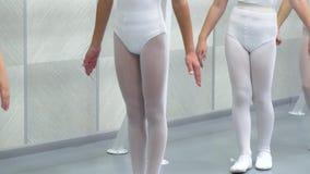 Τα πόδια κινηματογραφήσεων σε πρώτο πλάνο των μικρών ballerinas ομαδοποιούν στα άσπρα παπούτσια εν ενεργεία στο σχολείο μπαλέτου  φιλμ μικρού μήκους