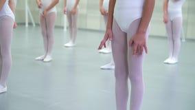 Τα πόδια κινηματογραφήσεων σε πρώτο πλάνο των μικρών ballerinas ομαδοποιούν στα άσπρα παπούτσια εν ενεργεία στο σχολείο μπαλέτου  απόθεμα βίντεο