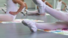 Τα πόδια κινηματογραφήσεων σε πρώτο πλάνο των μικρών ballerinas ομαδοποιούν στα άσπρα παπούτσια εν ενεργεία στο πάτωμα στο σχολεί απόθεμα βίντεο