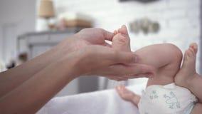 Τα πόδια μωρών στα χέρια φροντίδας του mom κοντά επάνω, νεογέννητο κορίτσι στις πάνες κινούνται ενεργά στο μεταβαλλόμενο πίνακα απόθεμα βίντεο