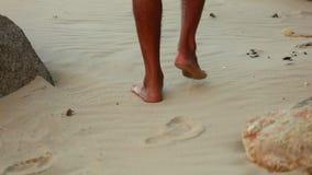 Τα πόδια περιπατητών σε μια άσπρη αμμώδη παραλία με τους βράχους ξεραί απόθεμα βίντεο
