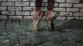 Τα πόδια στα χρυσά παπούτσια pointe είναι μπαλέτο ενεργά χορού δίπλα στον άσπρο τουβλότοιχο απόθεμα βίντεο