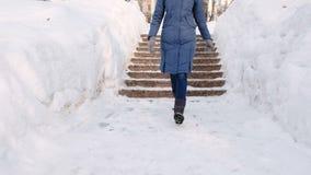 Τα πόδια της γυναίκας κινηματογραφήσεων σε πρώτο πλάνο πηγαίνουν κάτω σε μια χιονώδη σκάλα, σκάλα Χειμερινό πάρκο στην πόλη κατά  φιλμ μικρού μήκους